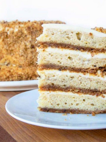 slice of banana crunch cake on a white plate in front of the whole cake