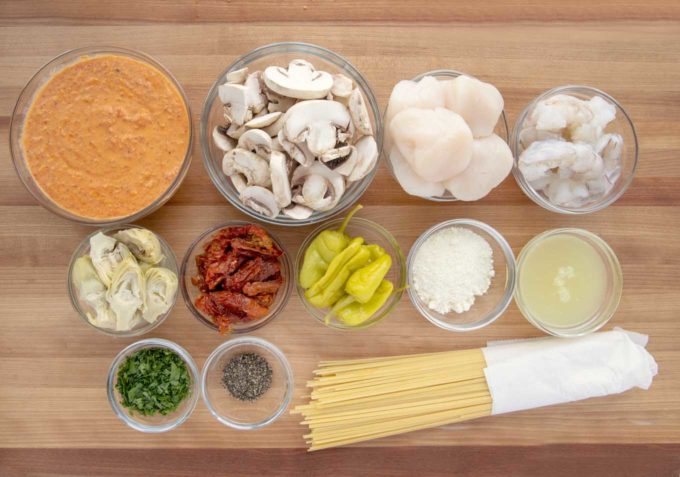overhead view of ingredients to make shrimp and scallops with a roasted red pepper sauce over linguine
