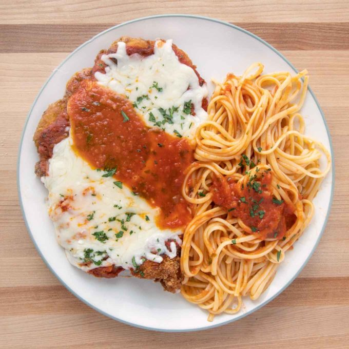 Chicken parm with linguinne on a white plate