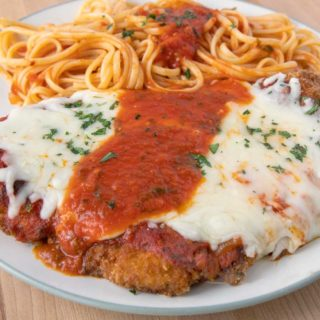 chicken parm on a white plate with pasta