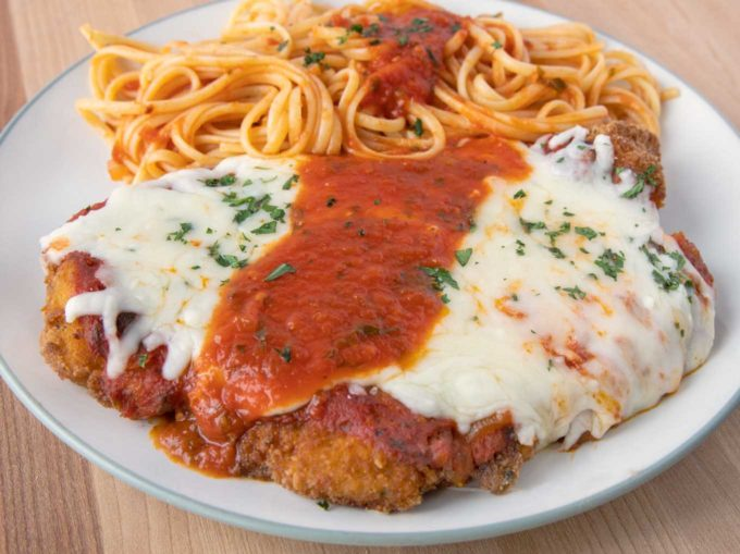 chicken parm and pasta on a green rimmed white plate
