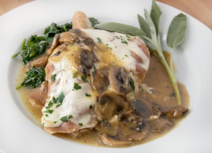 close up of chicken saltimbocca on a white plate