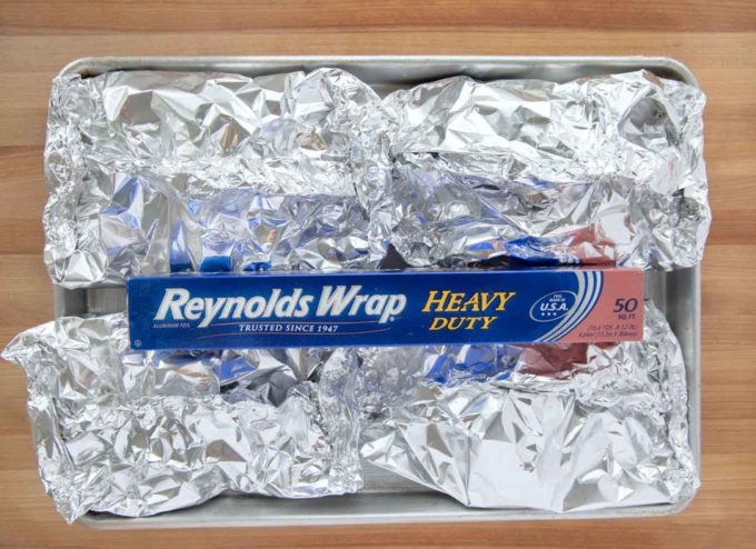 4 foil packets with on a sheet pan with a box of Reynolds foil on top
