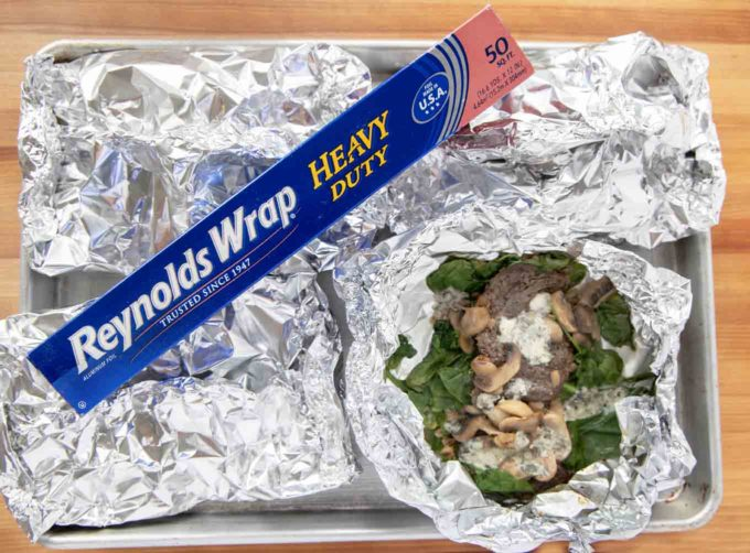 4 foil packets with one open showing the finished skirt steak on a sheet pan with a box of Reynolds foil across on the top