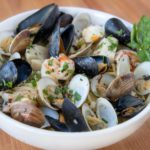 Frutta di mare with a sprig of basil in a white bowl
