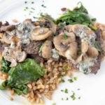 pan seared steak on a bed of farro topped with spinach mushrooms and blue cheese served on a white plate