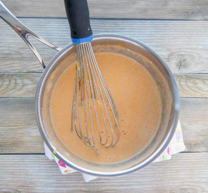 cheese sauce in pot with a wire whisk