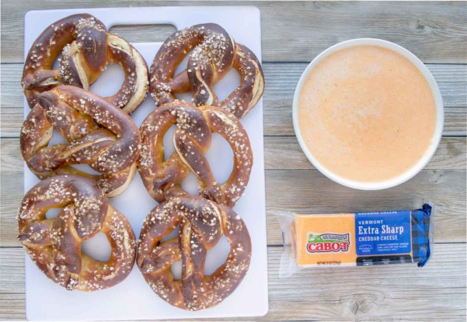tavern beer pretzels next to a bowl of beer cheese sauce and a block of Cabot cheddar cheese