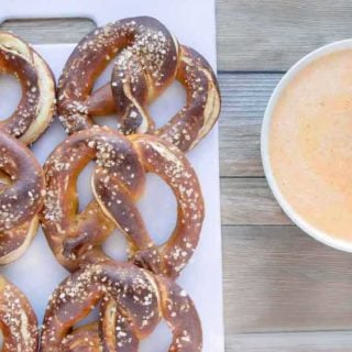 beer pretzels on a white tray with a bowl of cheddar sauce next to it