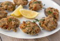 deviled clams on a white plate with lemon wedges