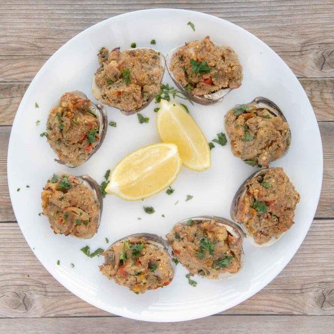 cooked deviled clams on a white plate with lemon wedges