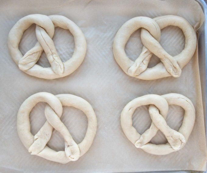 formed raw pretzels on a baking sheet