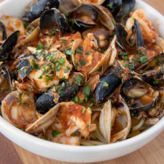 seafood marinara over pasta in a white bowl