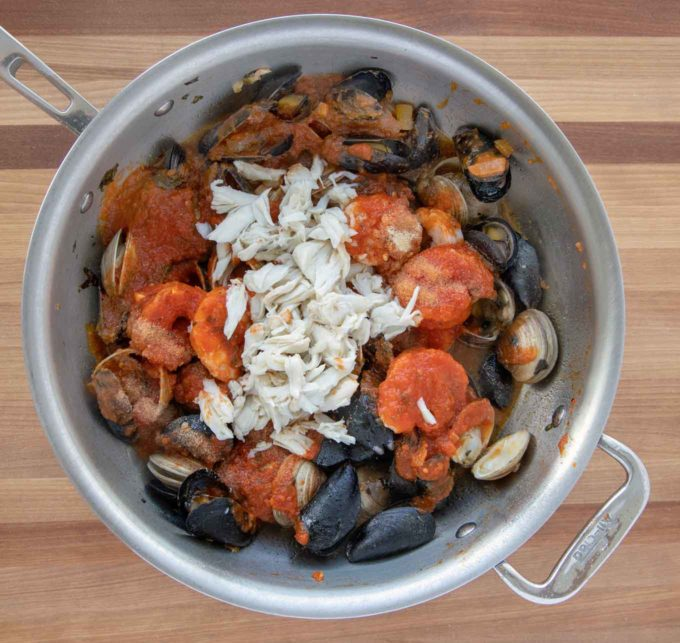 marinara sauce and crabmeat added to the cooked seafood in the pot