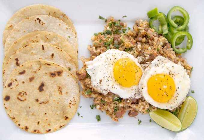 cowboy fried rice topped with fried eggs on a white platter with tortillas