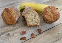 banana pecan muffins with bananas in the background