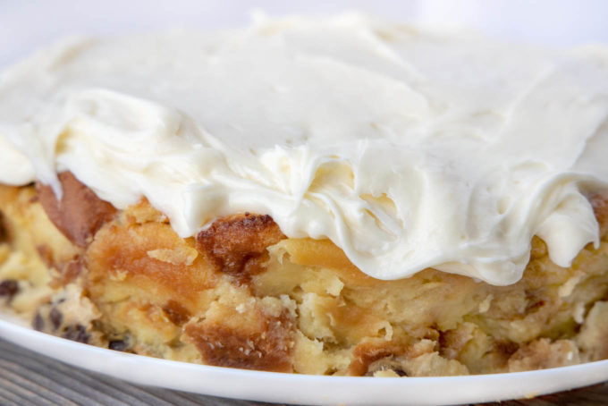 side view of bread pudding topped with cream cheese frosting