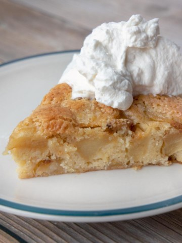slice buttery apple cake with whipped cream on a plate