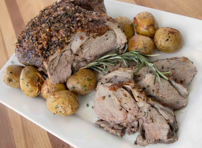 roast leg of lamb and slices with whole baby potatoes on a white platter