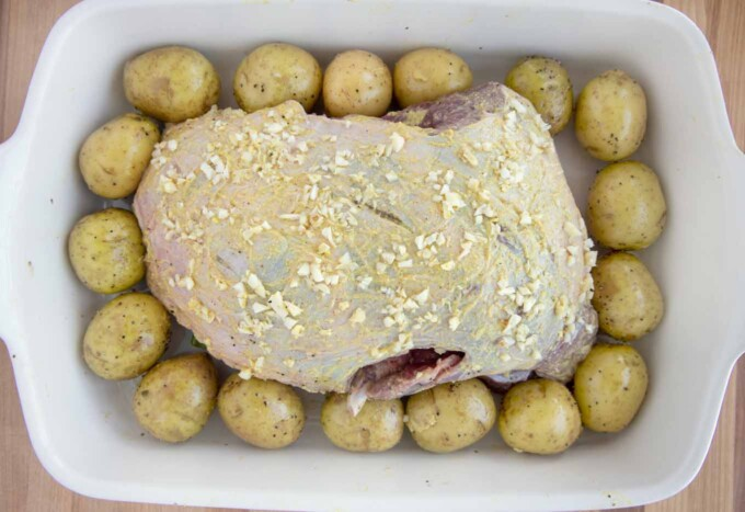 leg of lamb coated with mustard and chopped garlic in a pan with baby potatoes around the roast