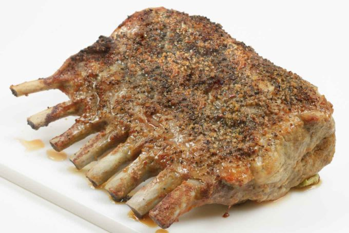 roasted rack of pork with a montreal seasoning crust on a white cutting board