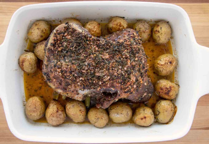 roasted leg of lamb and potatoes in a baking dish