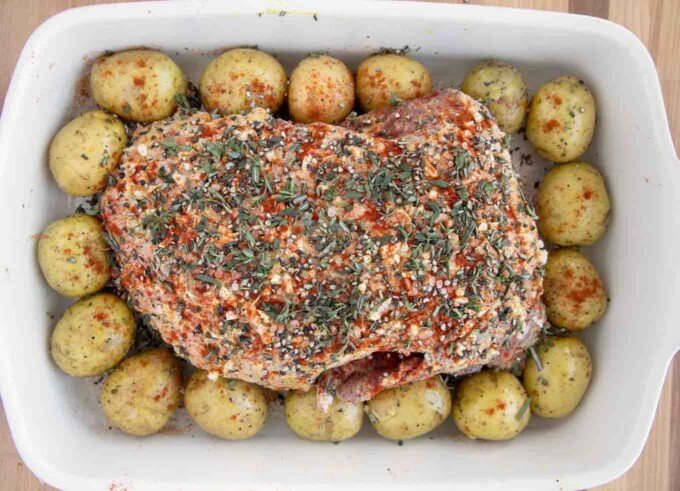 seasoned leg of lamb in a baking pan surrounded by baby potatoes
