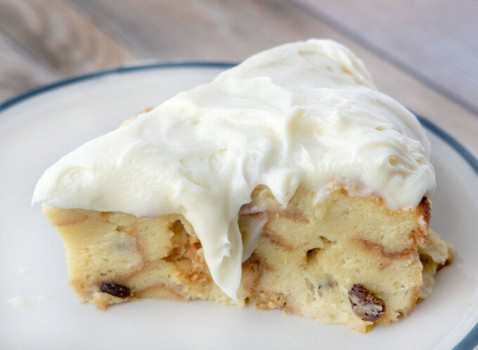 slice of bread pudding topped with cream cheese frosting on a white plate