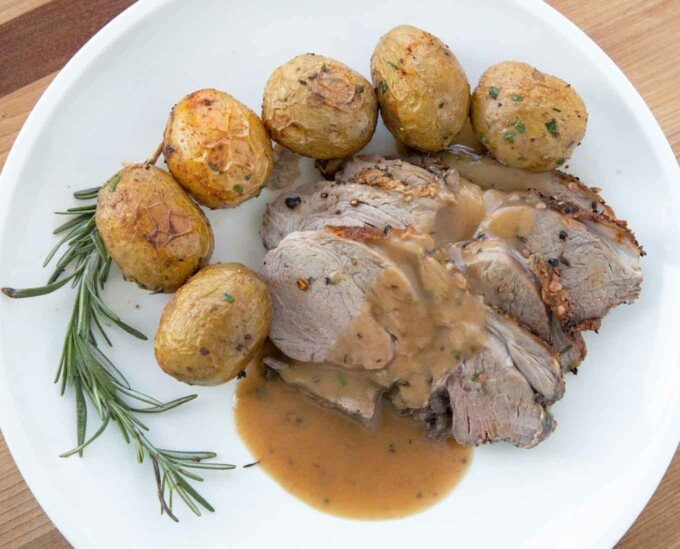 sliced leg of lamb with gravy along side whole baby potatoes and a sprig of rosemary on a white plate