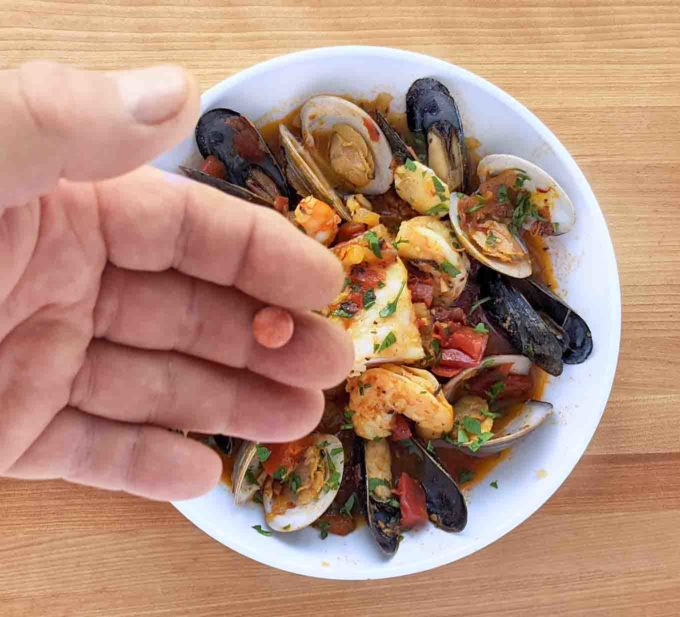 hand holding omeprazole odt above a bowl of Spanish seafood stew