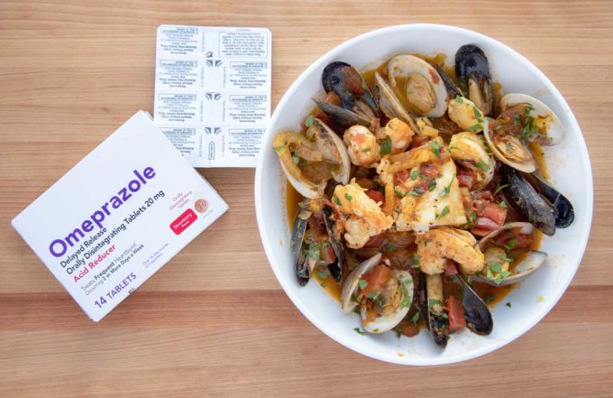 seafood stew in a white bowl next to a box of Omeprazole ODT