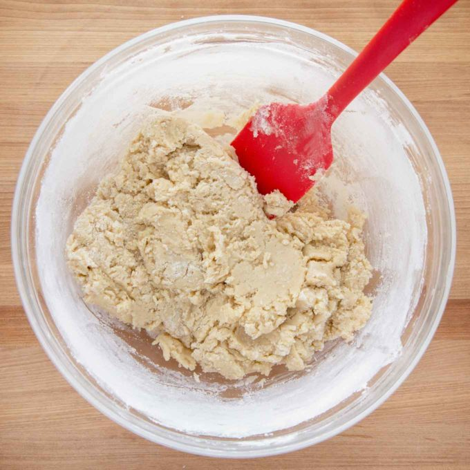 biscotti dough in a glass bowl with a red spatula