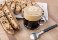 glass cup of coffee with biscotti on a tray and a spoon