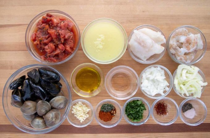 ingredients to make Spanish seafood stew in glass bowls