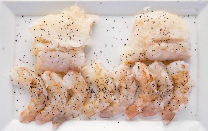 shrimp and cod seasoned with salt and pepper on a white platter