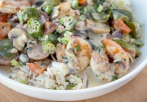close up of shrimp and sausage over rice in a white bowl