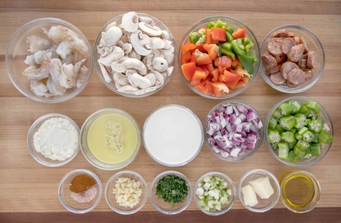 ingredients to make shrimp and sausage in glass bowls