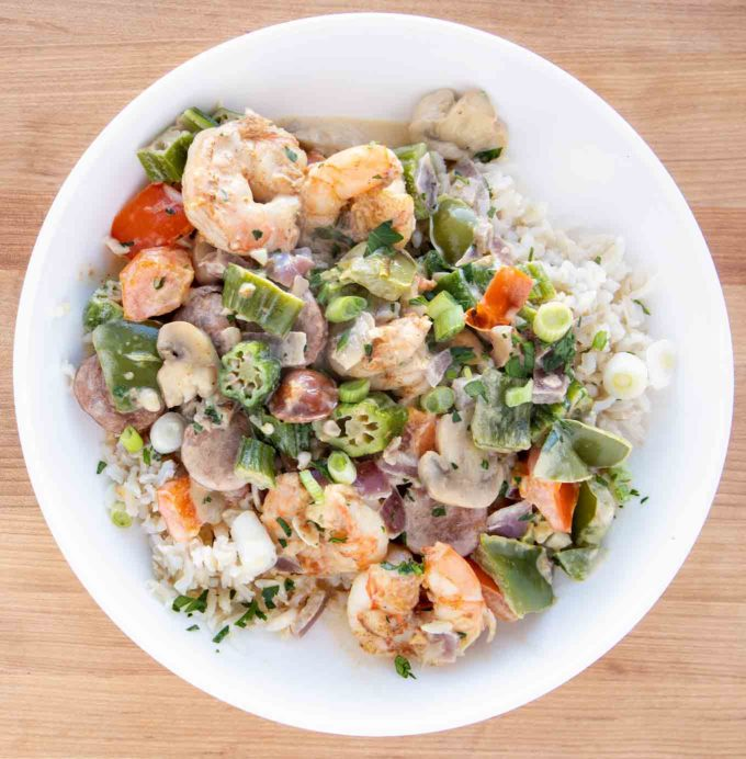 overhead shot of shrimp and sausage over rice in a white bowl