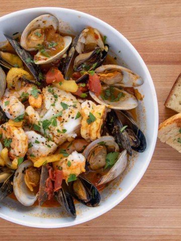bowl of seafood stew next to garlic toast
