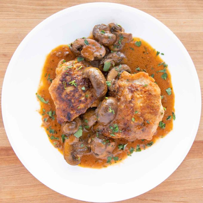 overhead shot of chicken chasseur on a white plate