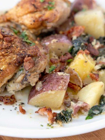 Tuscan Chicken with potatoes, baby kale and sun dried tomatoes on a white plate