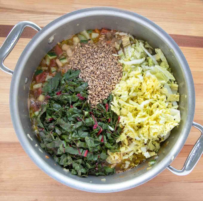 greens and farro added to pot