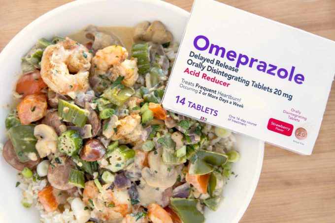 white bowl with cajun style shrimp and sausage  over rice, with a package of omeprazole sitting on the bowl