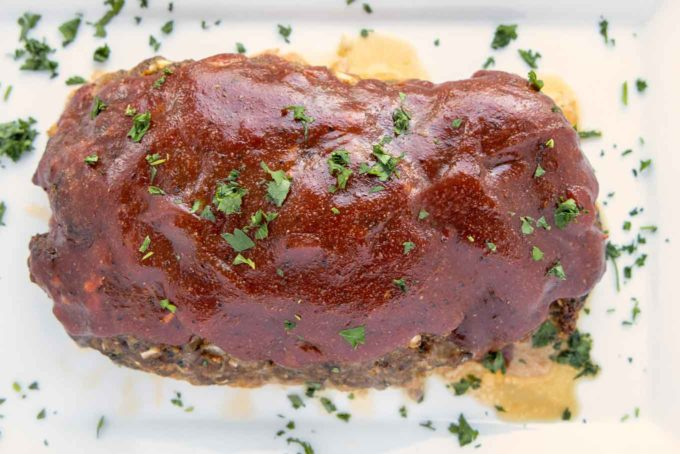 finished meatloaf garnished with chopped parsley on a baking sheet