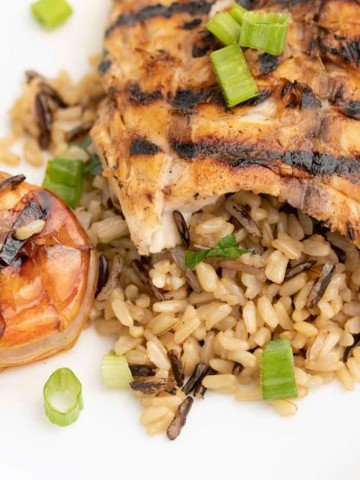 grilled rockfish on a bed of rice next to grilled shrimp on a white plate