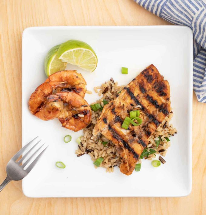 overhead view of grilled rockfish on a bed of rice next to grilled shrimp on a white plate