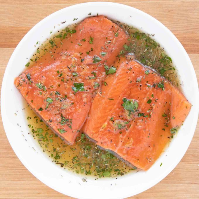 salmon marinating in a white deep bowl