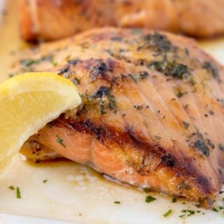crispy browned Irish whiskey salmon with a lemon wedge on a white platter