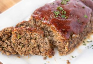 two slices of meatloaf in front of the rest of the meatloaf on a white platter