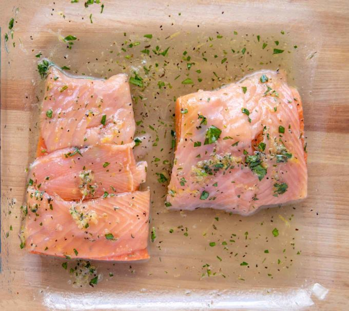 wrapped marinated salmon in glass baking dish with marinade